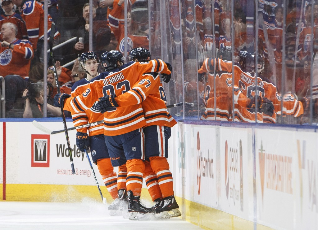 Edmonton Oilers' Ryan Nugent-Hopkins (93), Matthew Benning (83) and Connor McDavid (97) celebrate a goal against the Columbus Blue Jackets during firs...