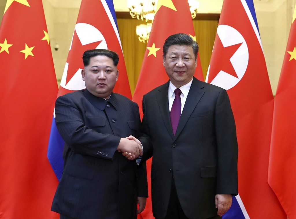 In this file photo provided Wednesday, March 28, 2018, by China's Xinhua News Agency, North Korean leader Kim Jong Un, left, and Chinese President Xi ...