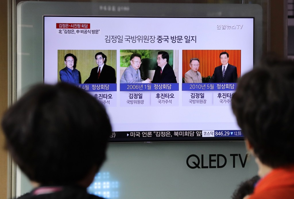 People watch a news program on TV reporting about the summits between North Korea and China at the Seoul Railway Station in Seoul, South Korea, Wednes...
