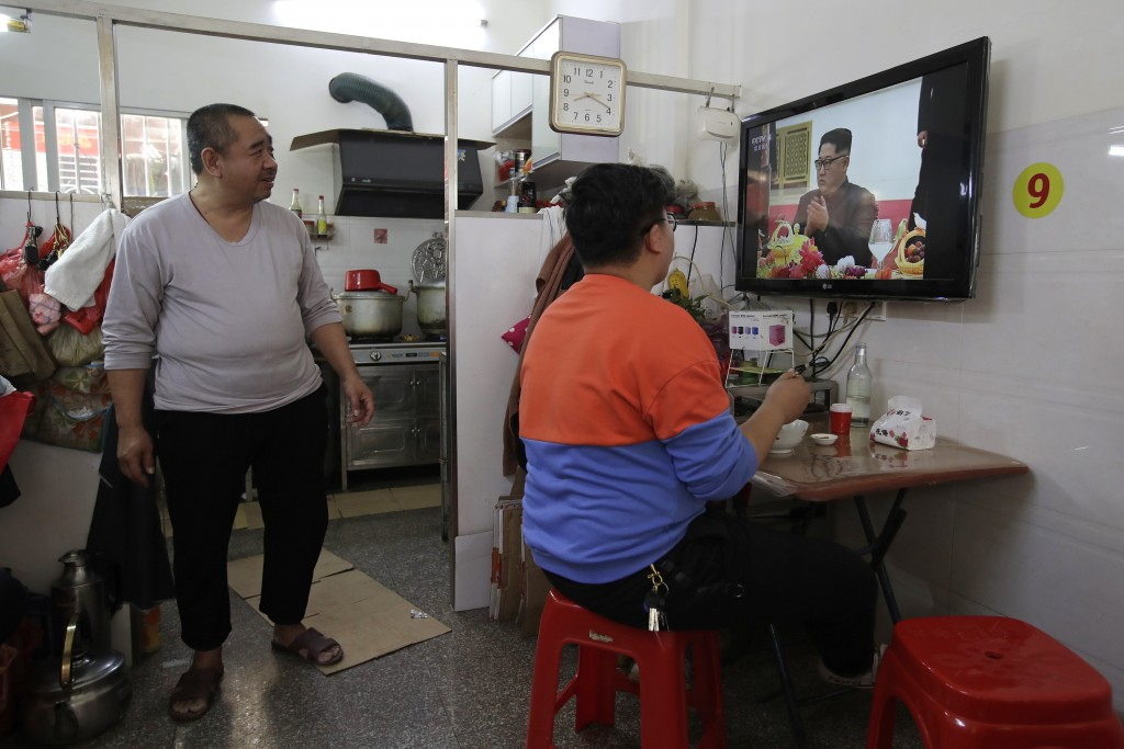 People watch CCTV morning news on TV reporting the visit by North Korean leader Kim Jong Un to China,  at a restaurant in Jiexi county in south China'...