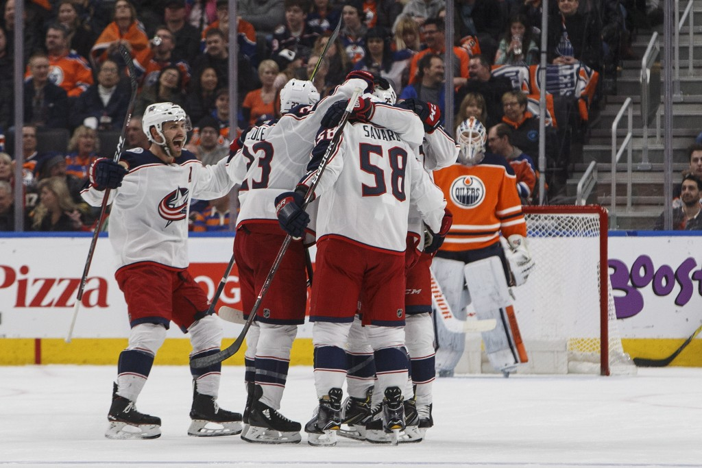 Columbus Blue Jackets players celebrate a goal as Edmonton Oilers goalie Cam Talbot (33) looks on during second period NHL hockey action in Edmonton, ...