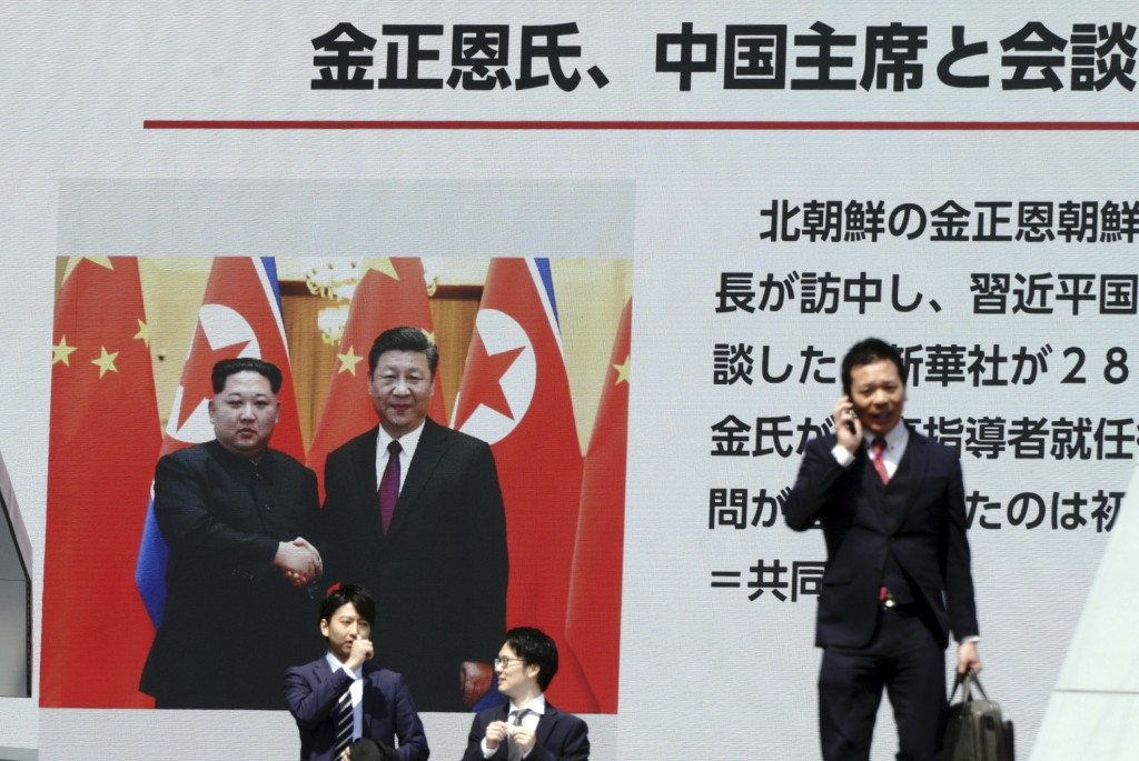 People walk past a public TV screen showing a footage of North Korean leader Kim Jong Un and Chinese President Xi Jinping during a news program in Tok...