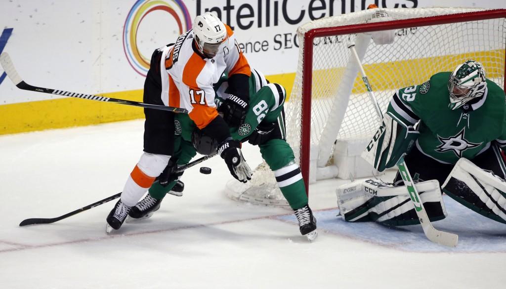 Philadelphia Flyers right wing Wayne Simmonds (17) hits Dallas Stars defenseman Stephen Johns (28) as Stars goaltender Kari Lehtonen (32) looks on dur...
