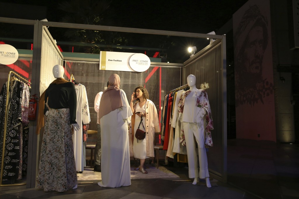 In this Wednesday, March 28, 2018 photograph, a woman visits a stand at a modest fashion show in Dubai, United Arab Emirates. The Islamic Fashion and