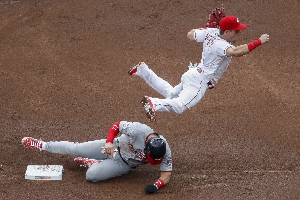 Cincinnati Reds second baseman Scooter Gennett, right, leaps over Washington Nationals' Bryce Harper after forcing him out in the first inning of an o...
