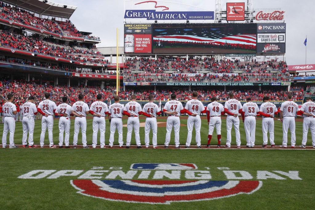 The Cincinnati Reds stand for the national anthem before an opening day baseball game against the Washington Nationals, Friday, March 30, 2018, in Cin...