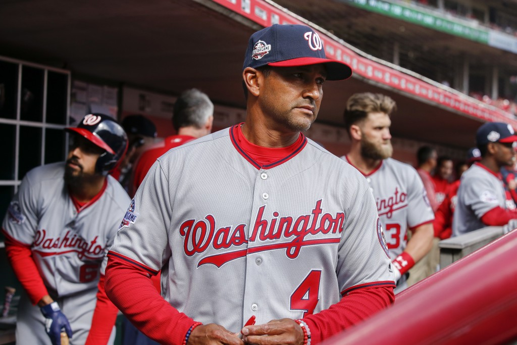 Washington Nationals manager Dave Martinez watches from the dugout before an opening day baseball game against the Cincinnati Reds, Friday, March 30, ...