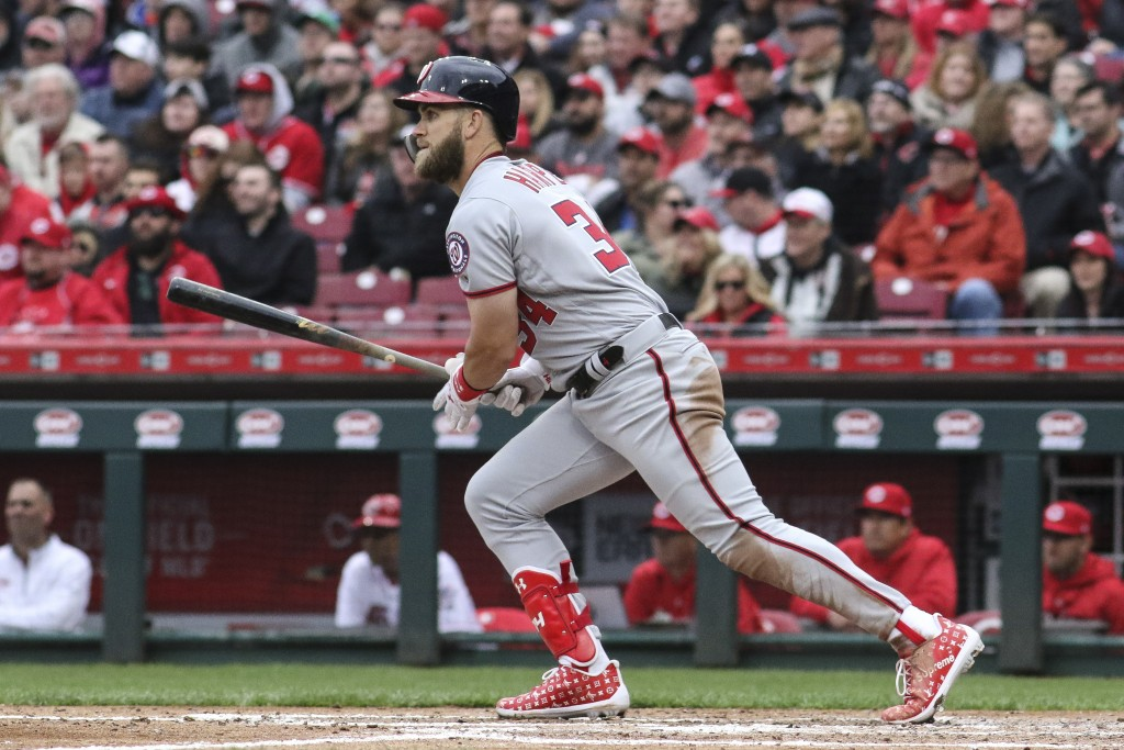 Washington Nationals' Bryce Harper hits a single off Cincinnati Reds starting pitcher Homer Bailey in the third inning of an opening day baseball game...