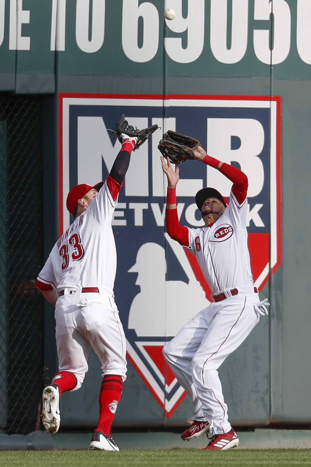 Cincinnati Reds center fielder Billy Hamilton, right, catches out Washington Nationals' Michael A. Taylor with bases loaded before colliding with righ...