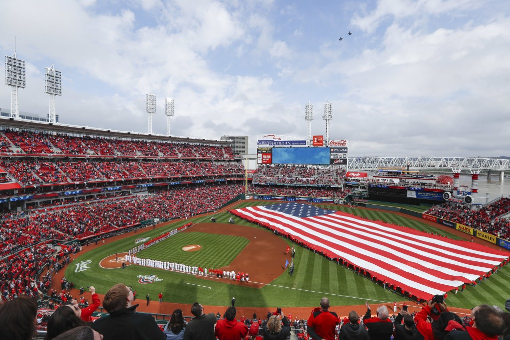 Spectators stand for the national anthem before an opening day baseball game between the Cincinnati Reds and the Washington Nationals, Friday, March 3...