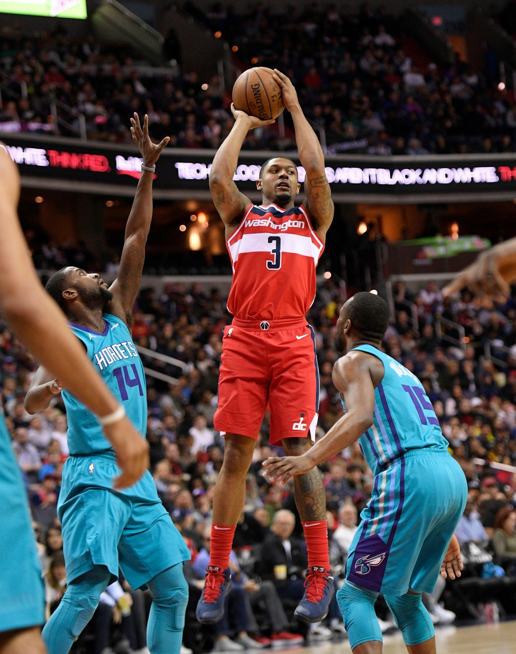 Washington Wizards guard Bradley Beal (3) looks to pass against Charlotte Hornets forward Michael Kidd-Gilchrist (14) and guard Kemba Walker (15) duri...