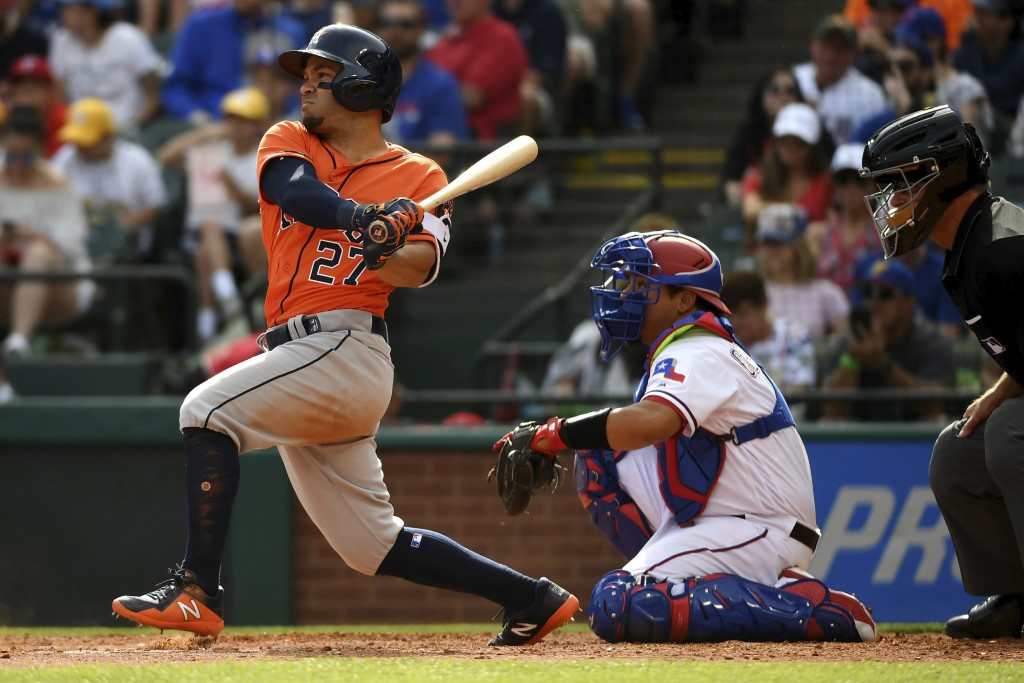 Houston Astros' Jose Altuve (27) follows through on a single as Texas Rangers catcher Juan Centeno and home plate umpire Ed Hickox look on in the fift...