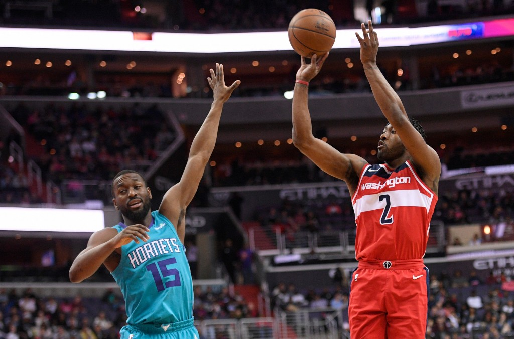 Washington Wizards guard John Wall (2) shoots over Charlotte Hornets guard Kemba Walker (15) during the second half of an NBA basketball game, Saturda...