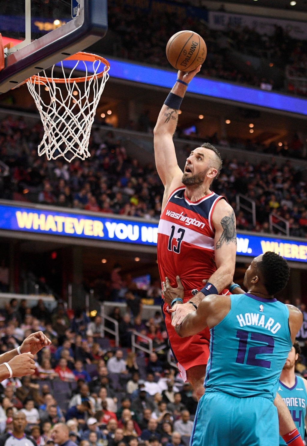 Washington Wizards center Marcin Gortat (13), of Poland, goes to the basket against Charlotte Hornets center Dwight Howard (12) during the second half