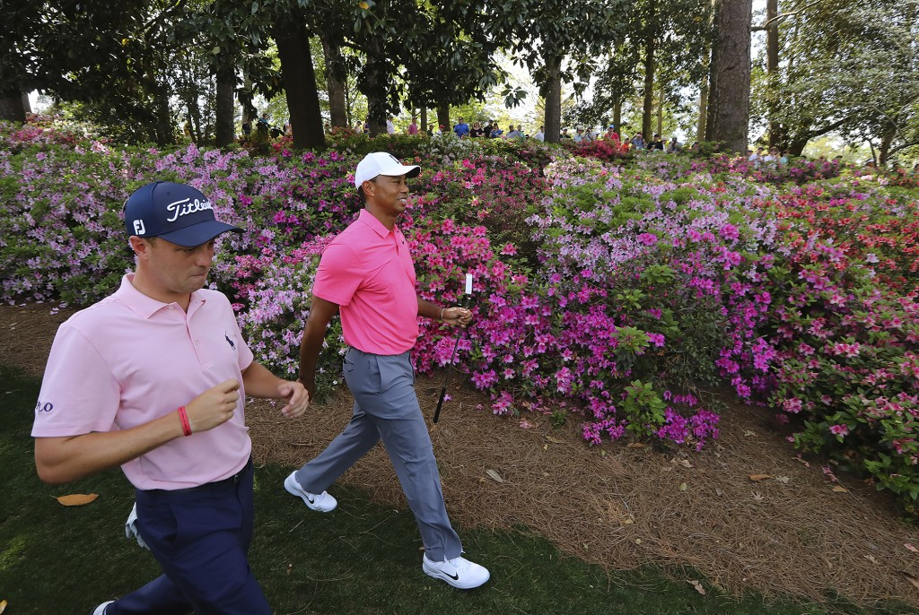 Justin Thomas, left, and Tiger Woods walk to the sixth green during practice for the Masters golf tournament at Augusta National Golf Club, Monday, Ap...