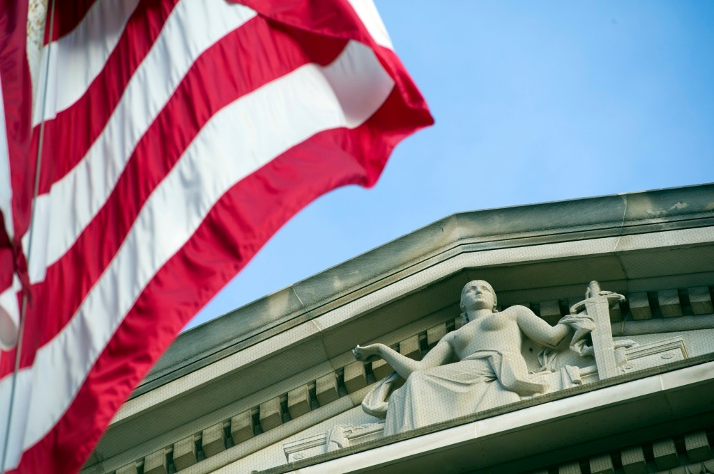 FILE - In this Nov. 2016 file photo, the American Flag flies outside the Justice Department in Washington. A new team of federal agents is targeting o...