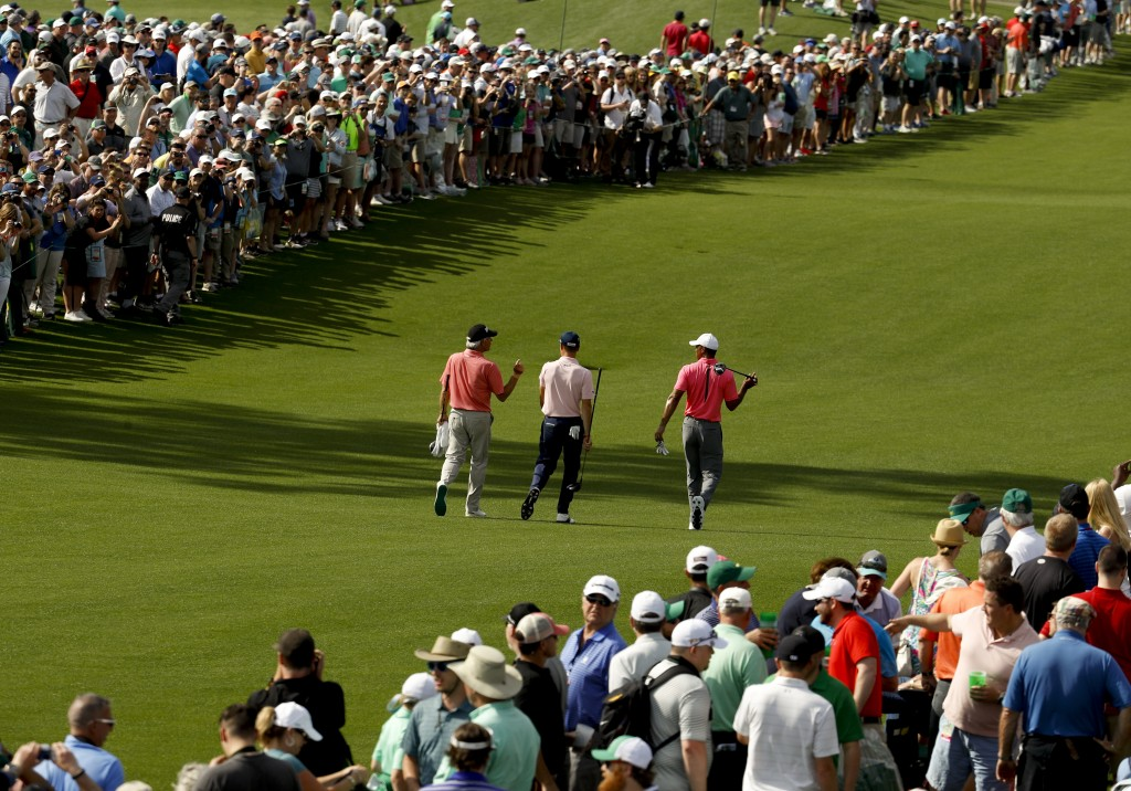 Fred Couples, from left, Justin Thomas and Tiger Woods walk to the eighth green during practice for the Masters golf tournament at Augusta National Go...