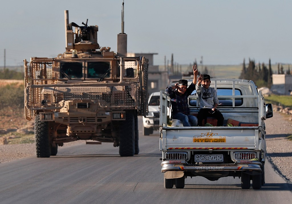 FILE -- In this Saturday, March 31, 2018 file photo, Syrian boys, right, sit on a pickup truck as they travel next to a U.S. vehicle, on a road leadin...