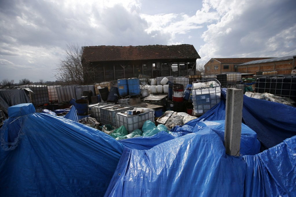 In this photo taken Monday, March 12, 2018, a view of old barrels and plastic containers full of liquid found at a farm in the northern town of Pancev...