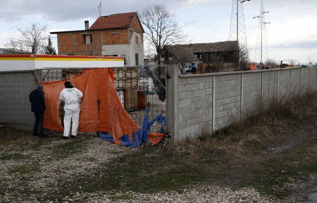 In this photo taken Monday, March 12, 2018, technicians inspect a farm where old barrels and plastic containers full of liquid were found in the north...
