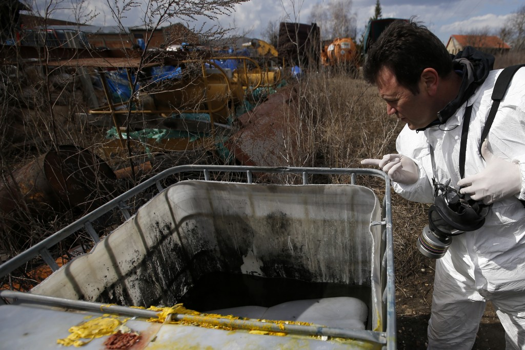 In this photo taken Monday, March 12, 2018, a technician inspects a container on a farm where old barrels and plastic containers full of liquid were f...