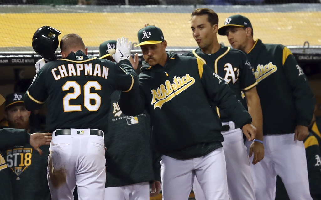 Oakland Athletics' Matt Chapman (26) is congratulated after scoring against the Texas Rangers during the fourth inning of a baseball game Wednesday, A...