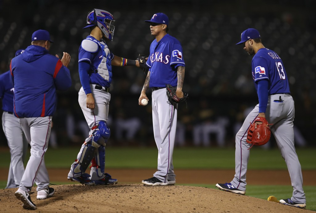 Texas Rangers pitcher Jesse Chavez, center, waits to be removed by manager Jeff Banister, left, during the seventh inning against the Oakland Athletic...