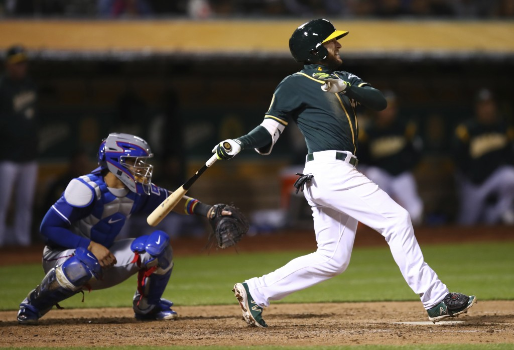 Oakland Athletics' Jed Lowrie follows through on a two-run single off Texas Rangers' Doug Fister during the fourth inning of a baseball game Wednesday...