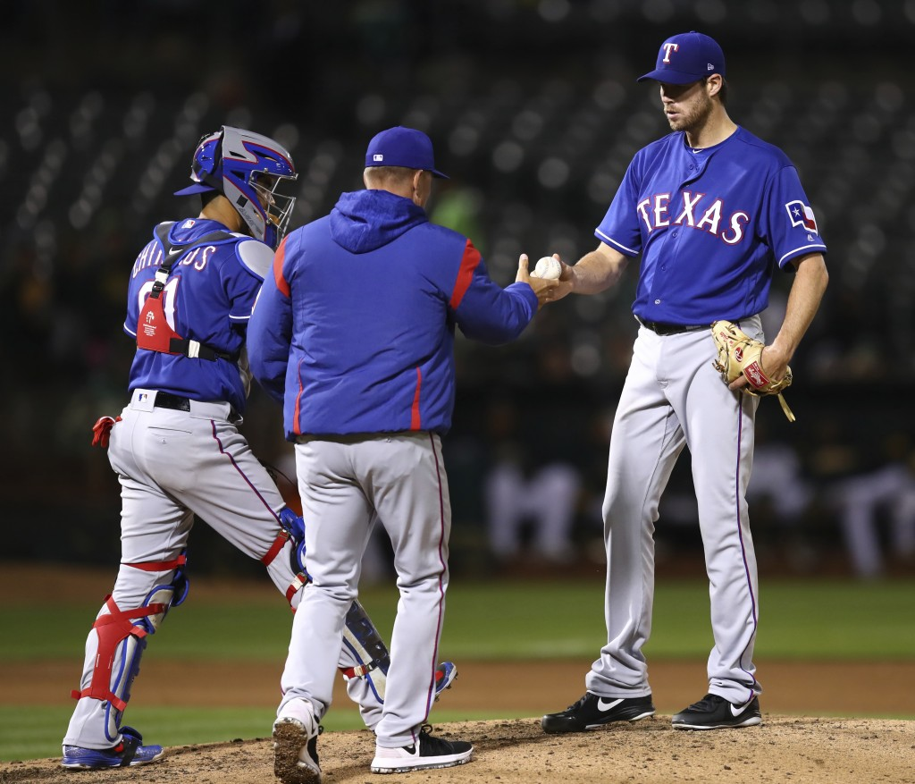 Texas Rangers pitcher Doug Fister, right, hands the ball to manager Jeff Banister as he is removed from the baseball game against the Oakland Athletic...