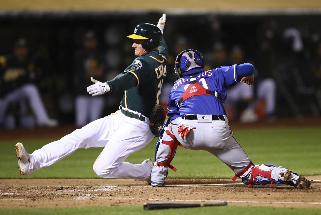 Oakland Athletics' Matt Chapman, left, scores past Texas Rangers catcher Robinson Chirinos during the fourth inning of a baseball game Wednesday, Apri...
