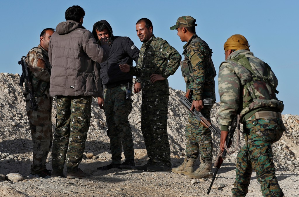 FILE - In this Thursday, March 29, 2018 file photo, commander Abu Ali Nejm, third right, of the U.S-backed Syrian Manbij Military Council, speaks with...