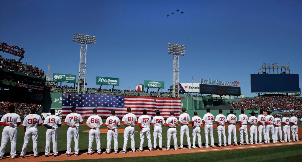 Boston Red Sox players line up along the first base line as four F-16's, from the Air National Guard's 134th Fighter Squadron in Burlington, Vermont, ...