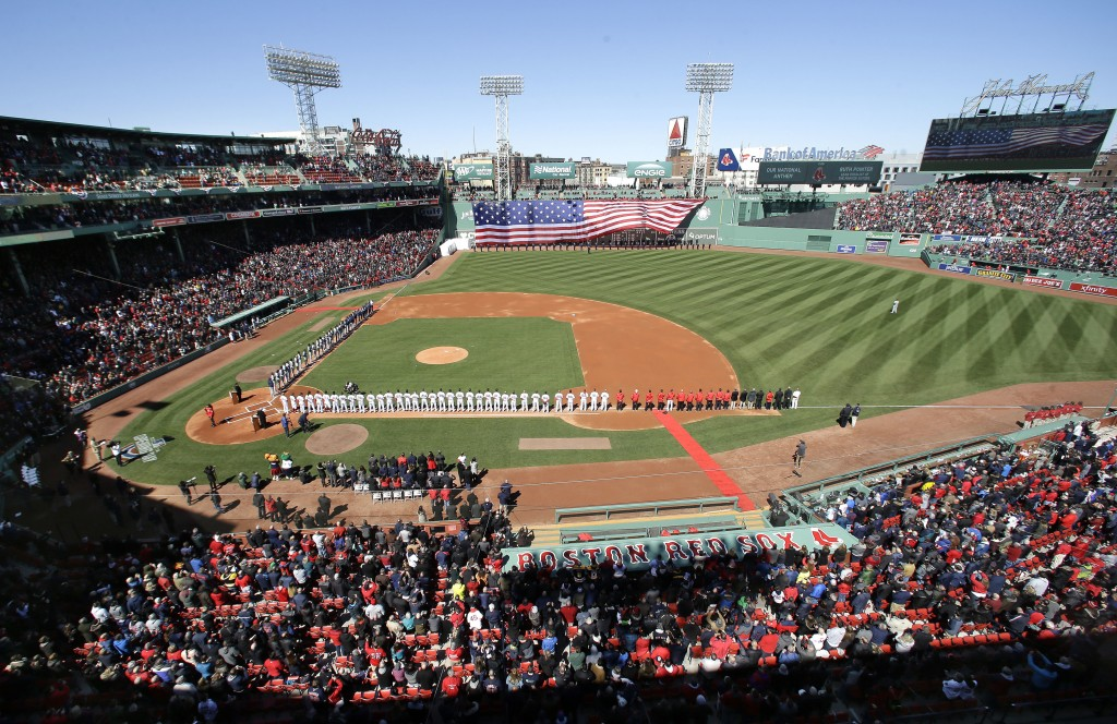 Members of the Tampa Bay Rays, center left, and Boston Red Sox, center right, line the baselines during ceremonies before a home opener baseball game,...