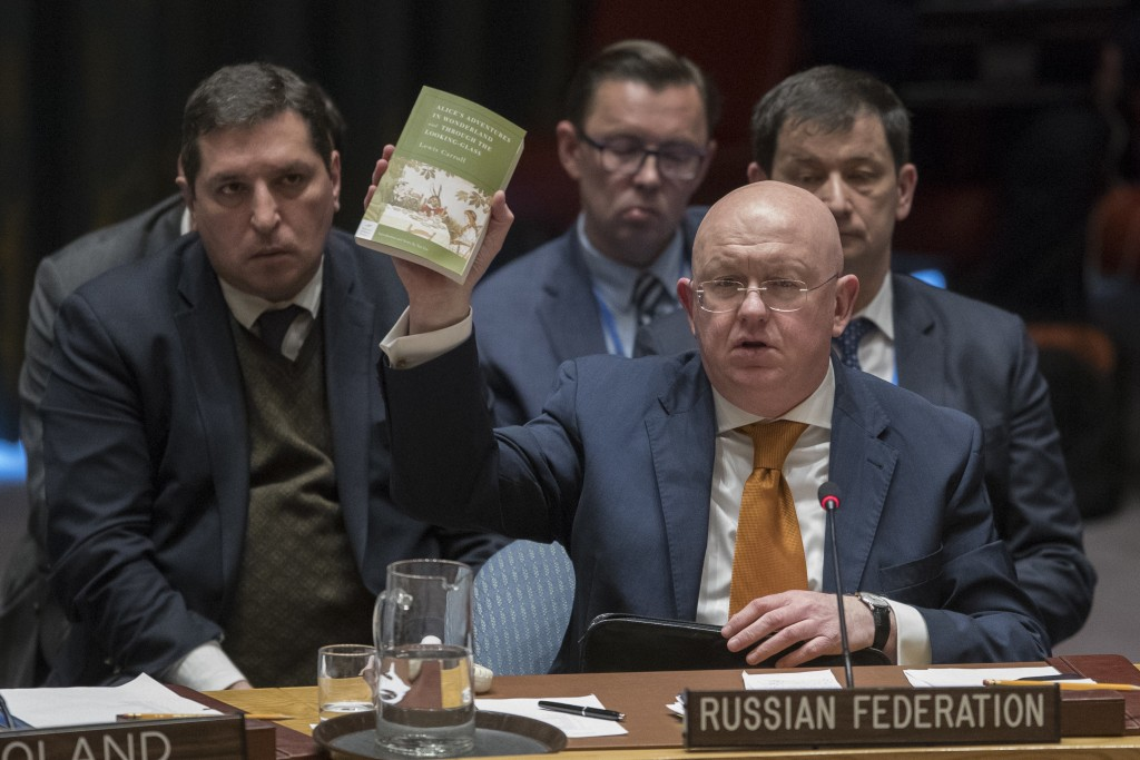 "Russian Ambassador to the United Nations Vassily Nebenzia holds up a copy of ""Alice's Adventures in Wonderland"" as he speaks during a Security Council"