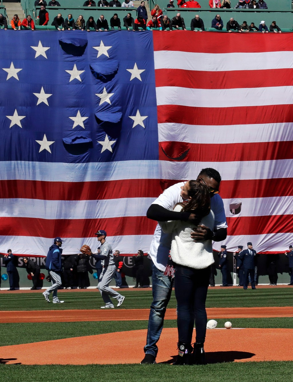 Olympic gold medalist Aly Raisman is embraced by former Boston Red Sox designated hitter David Ortiz during ceremonies prior to a home opener baseball...