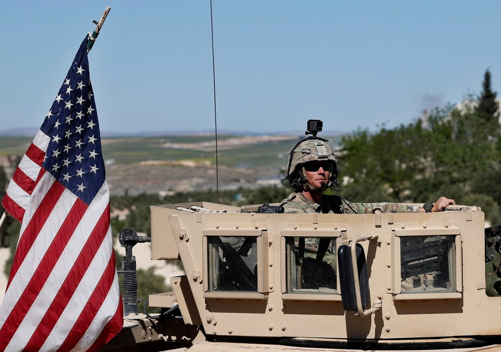 FILE - In this Wednesday, April 4, 2018 file photo, a U.S. soldier sits on his armored vehicle on a road leading to the tense front line with Turkish-...