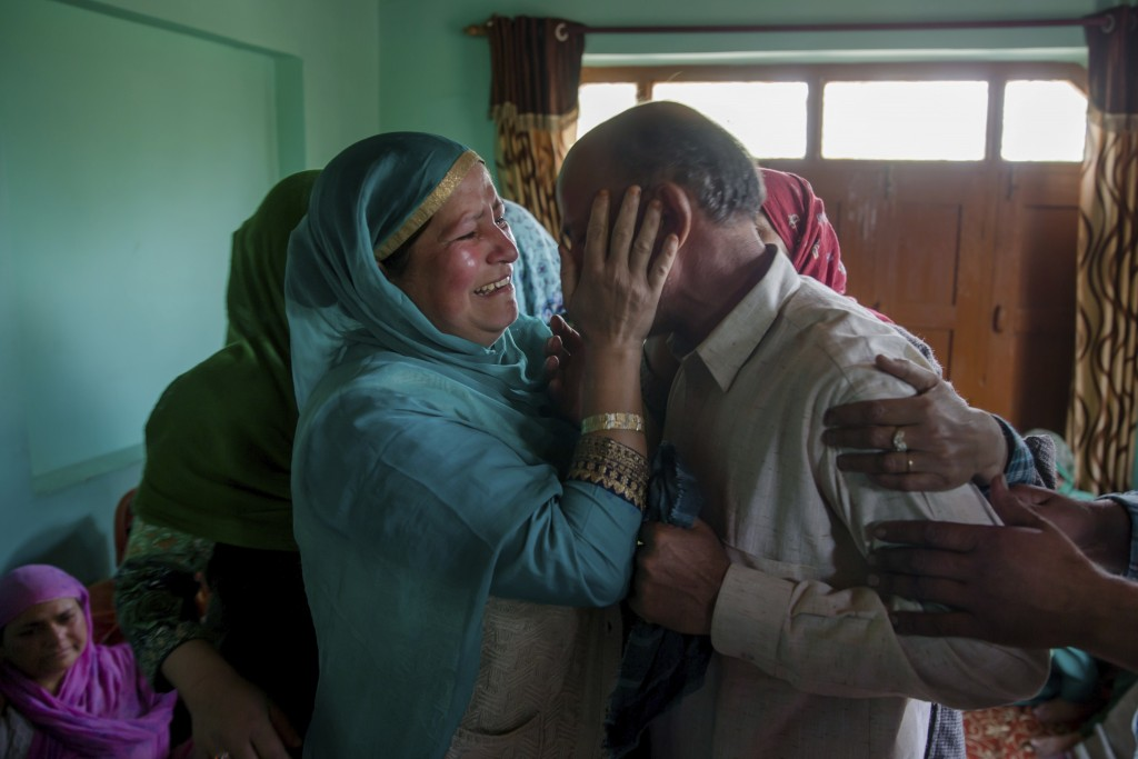 In this April 6, 2018, photo, a relative comforts Abdul Gaffar, the father of Manzoor Ahmed Bhat who was abducted and later killed by suspected milita...