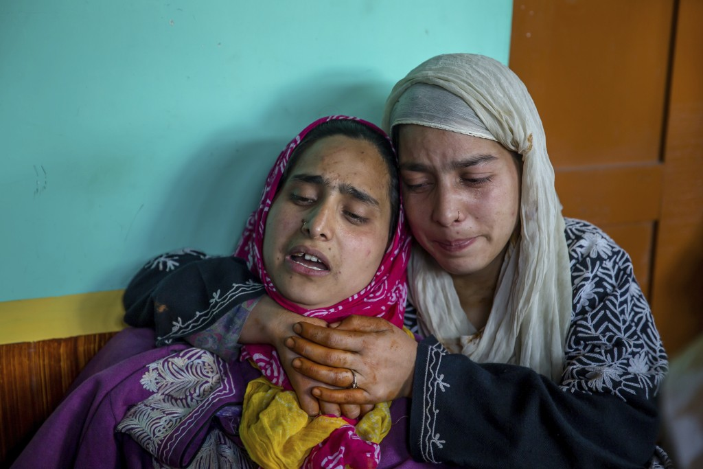In this April 6, 2018, photo, two Kashmiri women mourn the killing of their brother Manzoor Ahmed Bhat, who was abducted and later killed by suspected...