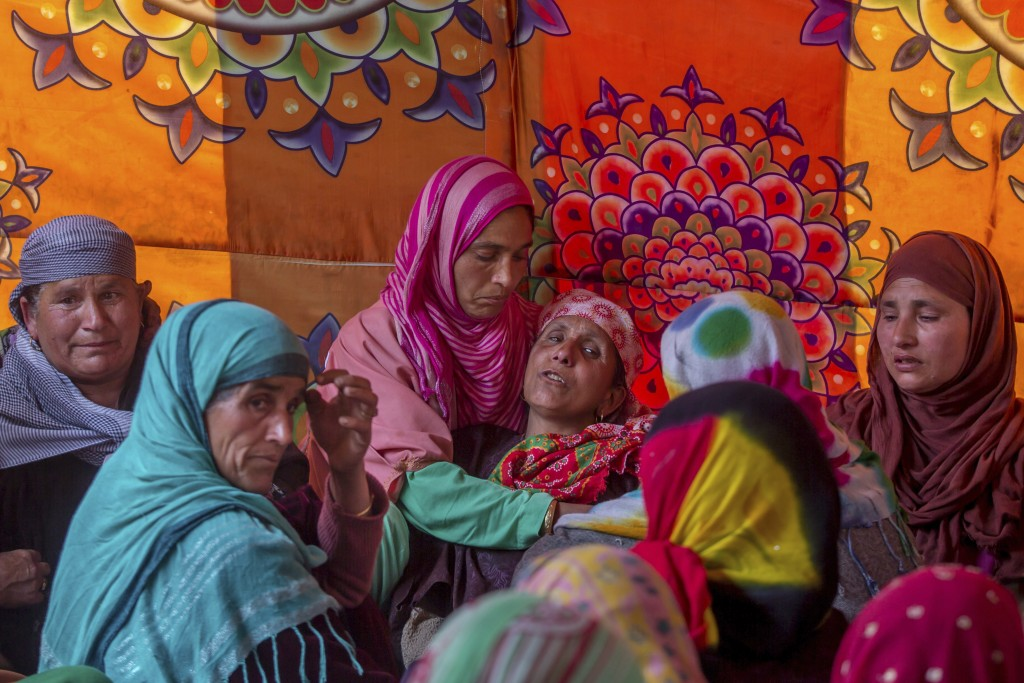 In this April 6, 2018, photo, relatives of Manzoor Ahmed Bhat, who was abducted and later killed by suspected militants, comfort his grieving mother, ...