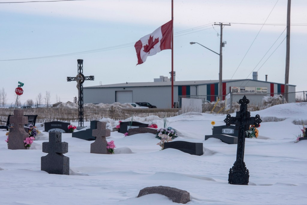 A large Canadian flag at half-mast is seen from a cemetery in Humboldt, Saskatchewan, on Sunday, April 8, 2018. Fifteen people traveling with the Humb...