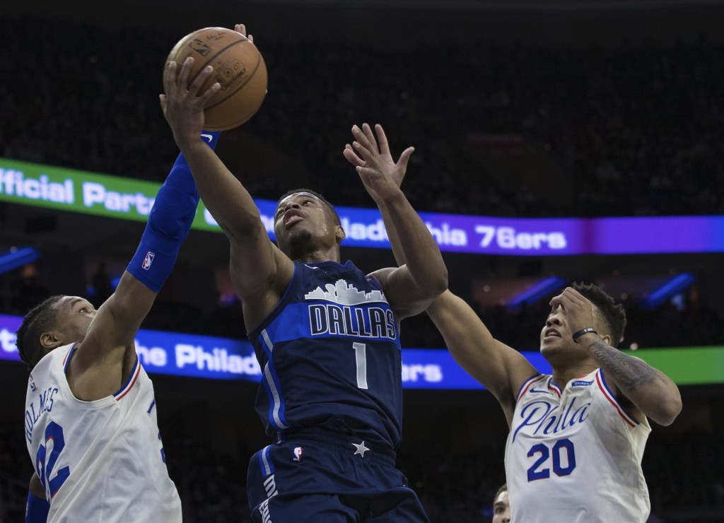 Dallas Mavericks' Dennis Smith Jr., center, shoots as Philadelphia 76ers' Richaun Holmes, left, and Markelle Fultz, right, defend during the first hal...
