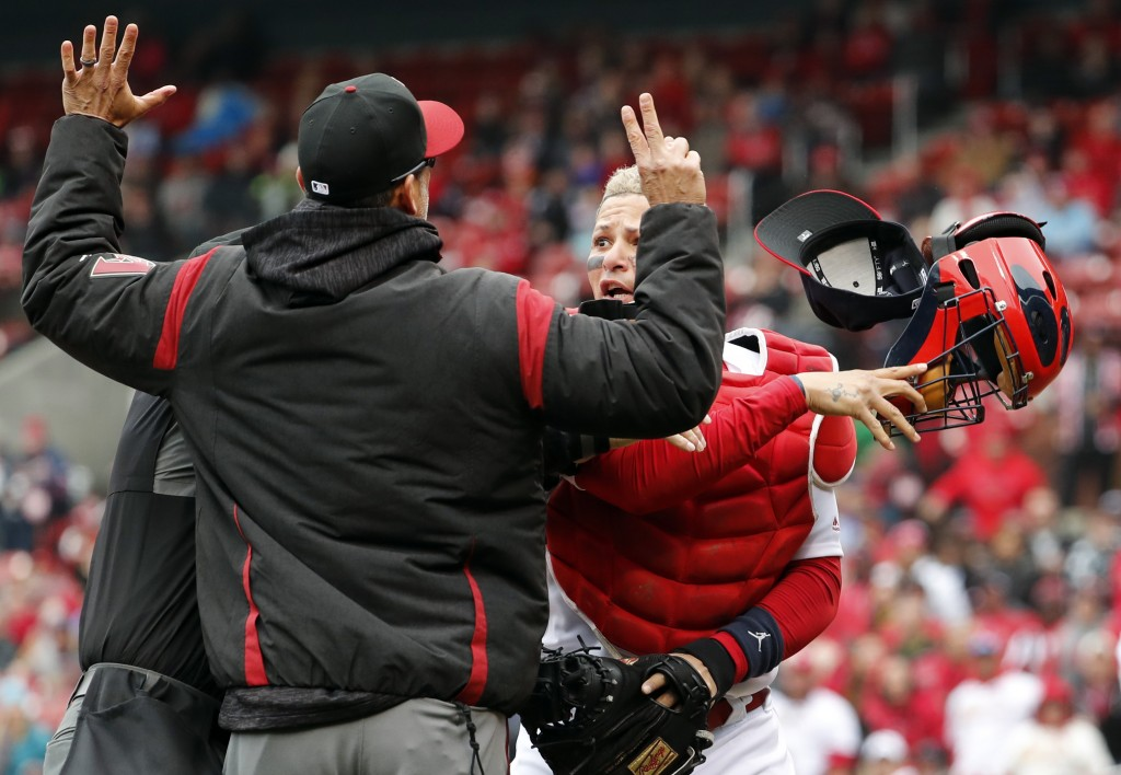 St. Louis Cardinals catcher Yadier Molina, right, throws off his mask as he argues with Arizona Diamondbacks manager Torey Lovullo during an altercati