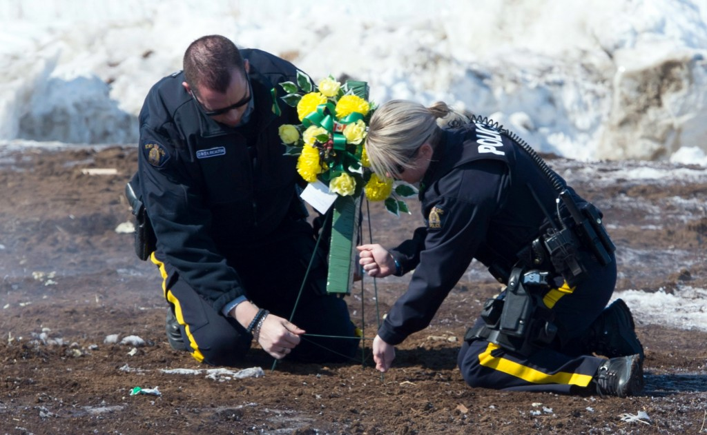 Members of the Royal Canadian Mounted Police lay flowers at the intersection of a crash site near Tisdale, Saskatchewan, Sunday, April, 8, 2018. A bus...