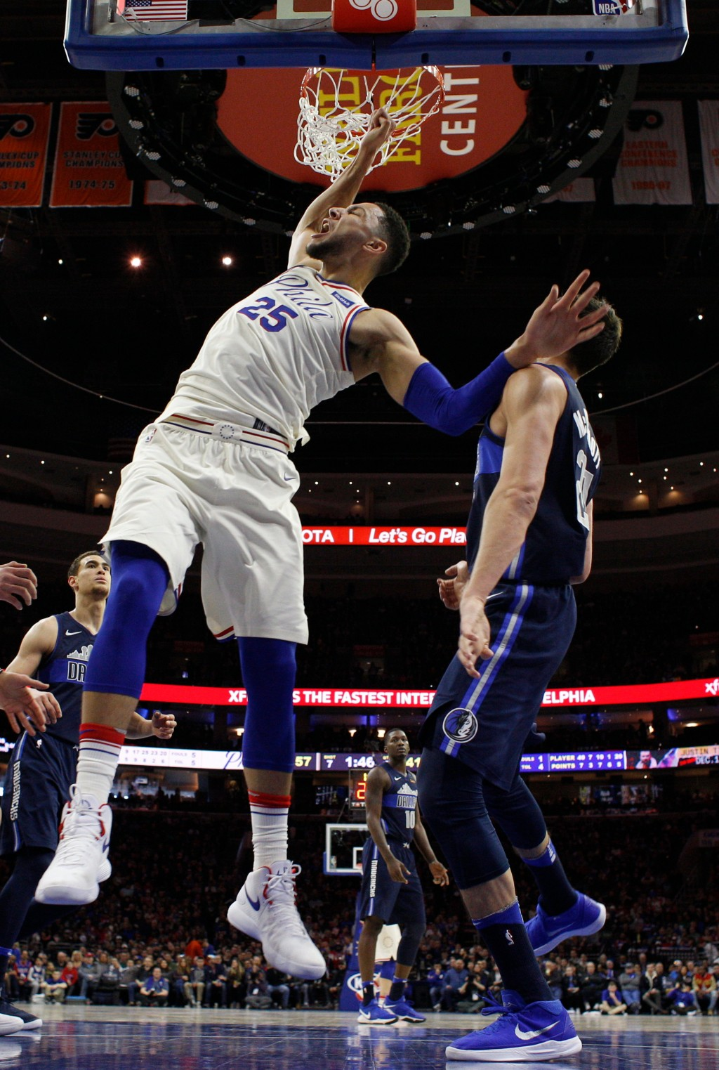 Philadelphia 76ers' Ben Simmons, left, of Australia, reacts after his dunk against Dallas Mavericks' Doug McDermott, right, during the first half of a...