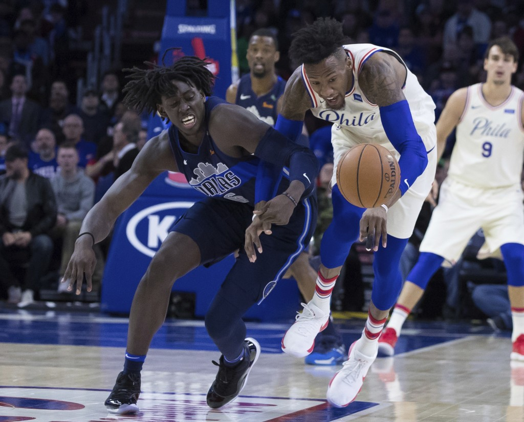 Philadelphia 76ers' Robert Covington, right, and Dallas Mavericks' Johnathan Motley, left, go after the ball during the first half of an NBA basketbal...