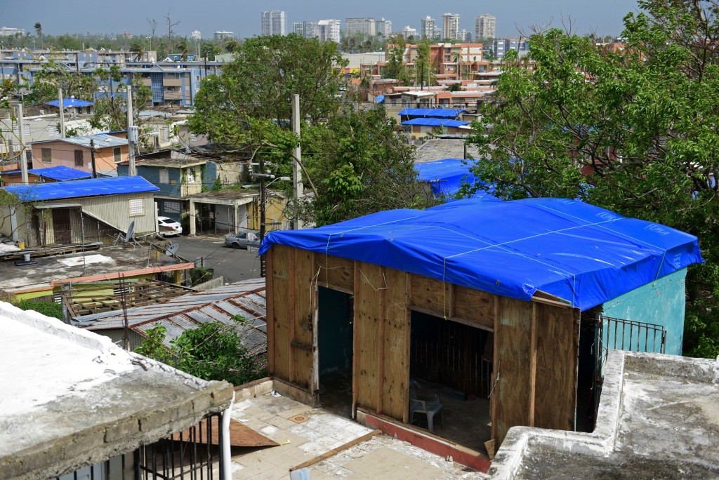 FILE - In this Oct. 19, 2017, file photo, homes in the Cantera area are covered with FEMA tarps, where buildings from the Hato Rey area stand in the b