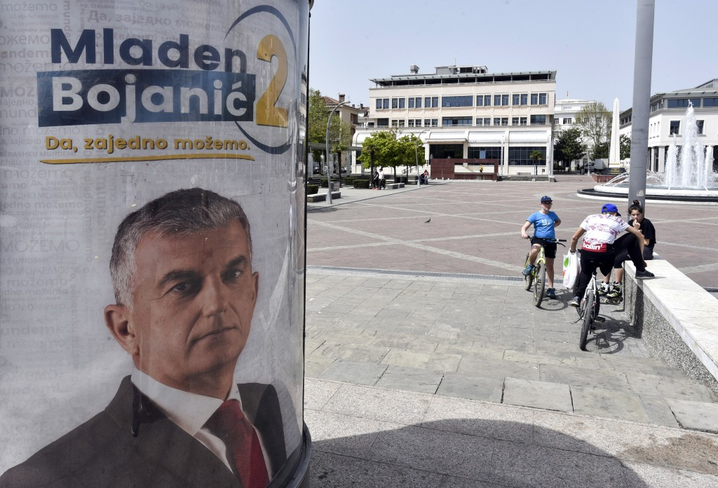 In this photo taken Thursday, April 12, 2018, people rest near a billboard showing Mladen Bojanic, backed by a diverse group of parties, including a p