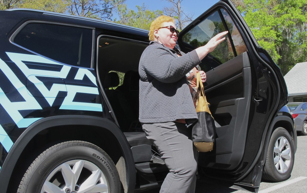In this photo taken March 7, 2018 shows Cinzhasha Farmer, who is blind, exiting a vehicle equipped with software meant to help the visually impaired i...