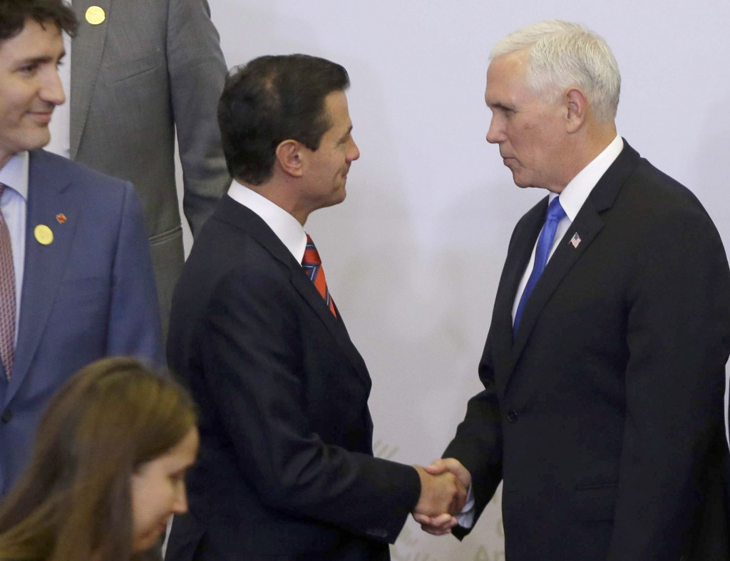 U.S. Vice President Mike Pence, right, shakes hands with Mexico's President Enrique Pena Nieto as they arrive for the group photo at Americas Summit i