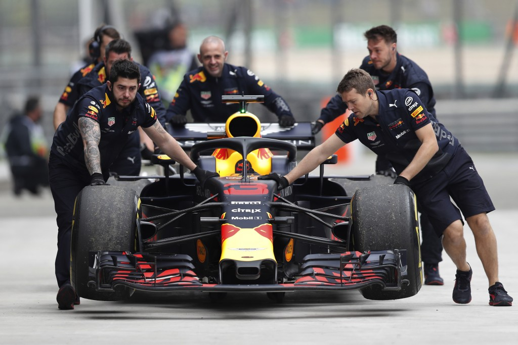 The car of Red Bull driver Daniel Ricciardo of Australia is pushed back to his team's garage after an engine trouble during the third practice session